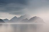 Summer cloudy Lofoten islands. Norway misty sea and fjords. Nordic rain.