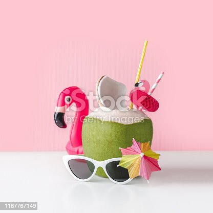 Fresh coconut on a pastel pink background with flamingo inflatable drink holder and sunglasses, summer vibes concept