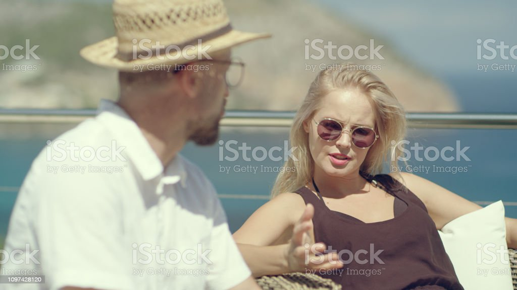 Couple relaxing on a terrace. Coastline view in background