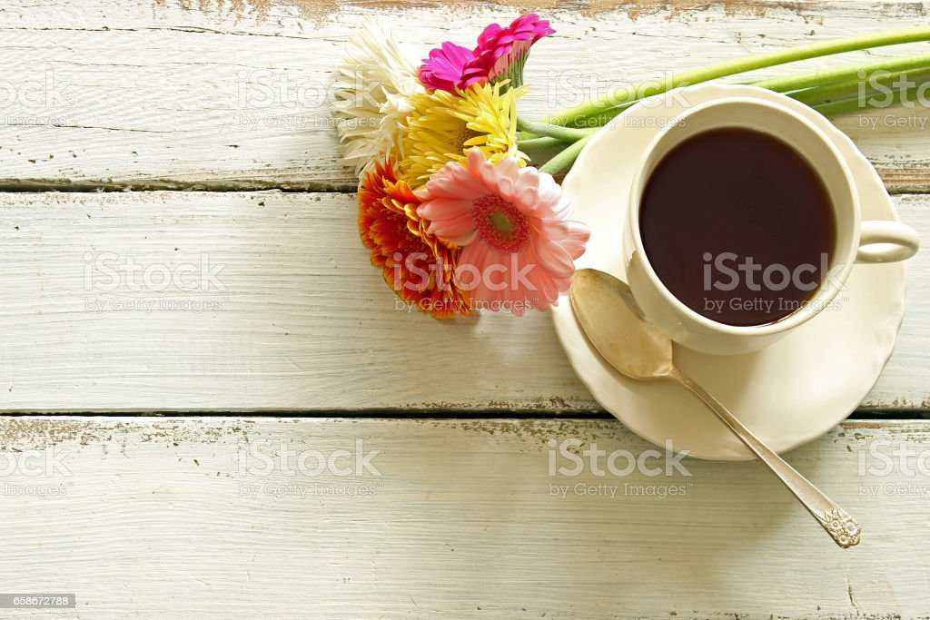 Simple cup of coffee with gerbera daisies against worn white wood...