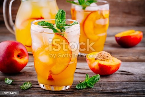 Summer cold drinks: homemade peach ice tea with ice cubes, and mint in glass on wooden background