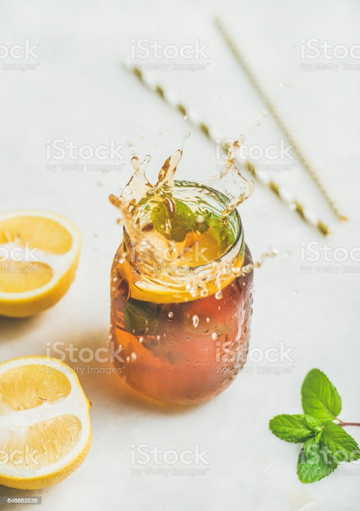 Summer cold Iced tea with lemon and herbs, vertical composition stock photo