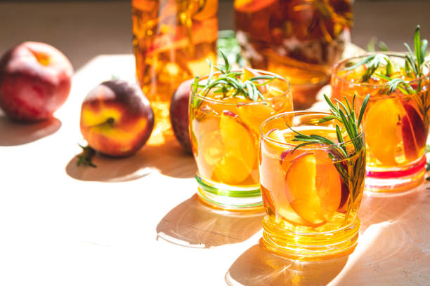 Summer cold peach fizz cocktail with rosemary stock photo