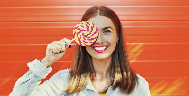 Summer colorful portrait of happy smiling young woman with lollipop over an orange background stock photo