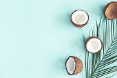 Summer composition. Coconut, palm leaf on pastel blue background. Summer concept. Flat lay, top view, copy space