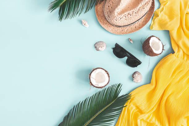 composizione estiva. foglie tropicali, vestito, cappello, cocco su sfondo blu. concetto estivo. lay piatto, vista dall'alto, spazio di copia - flat lay foto e immagini stock