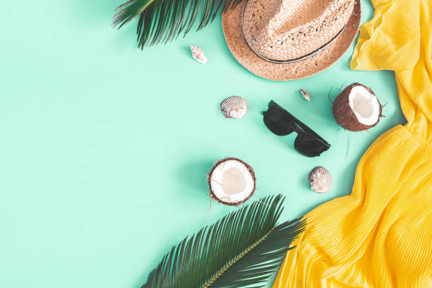 Summer composition. Tropical leaves, dress, hat, coconut on mint background. Summer concept. Flat lay, top view, copy space stock photo