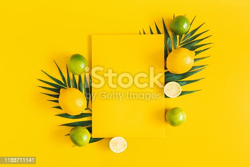 Summer composition. Tropical palm leaves, citrus fruits, yellow paper blank on yellow background. Summer concept. Flat lay, top view, copy space
