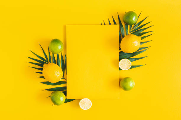 Summer composition. Tropical palm leaves, citrus fruits, yellow paper blank on yellow background. Summer concept. Flat lay, top view, copy space stock photo