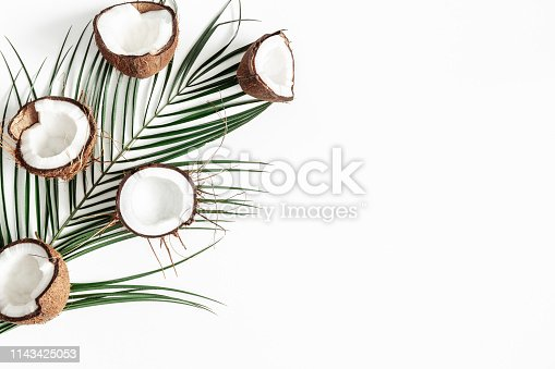 Summer composition. Tropical palm leaves, coconut on white background. Summer concept. Flat lay, top view, copy space