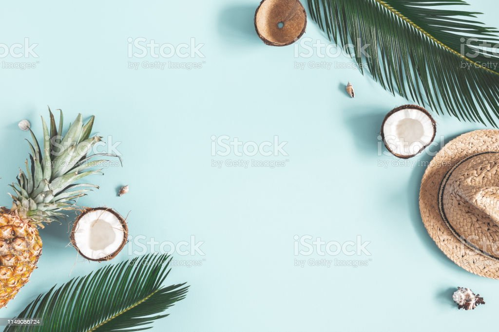 Summer composition. Tropical palm leaves, hat, fruits on blue background. Summer concept. Flat lay, top view, copy space - Zbiór zdjęć royalty-free (Ananas)