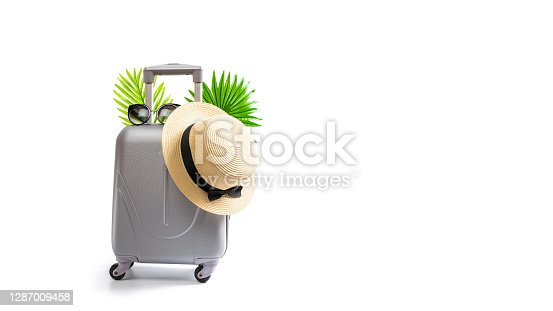 Summer concept background. Travel accessories with suitcase, straw hat, palm leaves in minimal trip vacation concept isolated on white. Copy space, summer vacation and business travel concept.