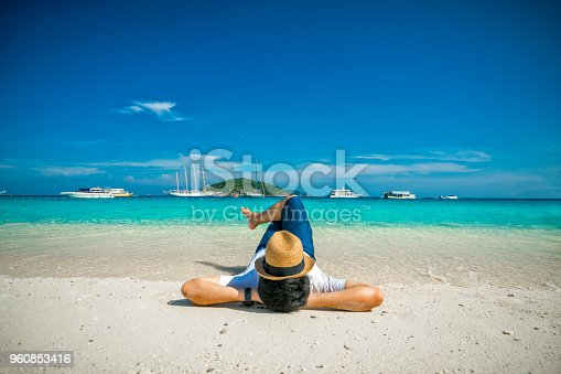 Young man traveler with hat on face sleeping with happiness and relaxing on beautiful tropical beach at Similan islands in Andaman sea at Phang Nga near Krabi and Phuket southern of Thailand in Summer