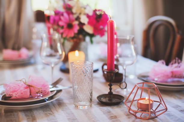 sommer-cottage-küche dekoriert für das festliche abendessen. romantische tischdekoration mit kerzen und blumen im rustikalen stil. - geheime garten parties stock-fotos und bilder