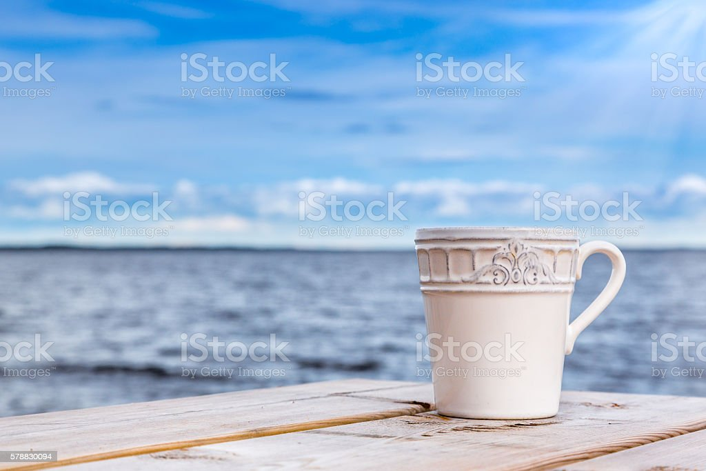 Summer, cup against horizon with blue sky and water. stock photo
