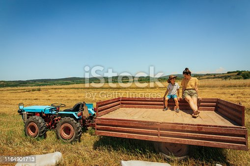 Mother and son on the tractor trailer during harvesting