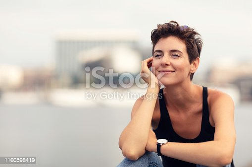A woman sitting by the quay in central Stockholm and enjoying a summer day.