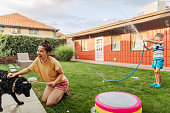 Photo of mother and son bathing their dog and splashing in the yard