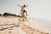 Photo is showing young father with his son, enjoying their fulfilled summer vacation by the ocean
