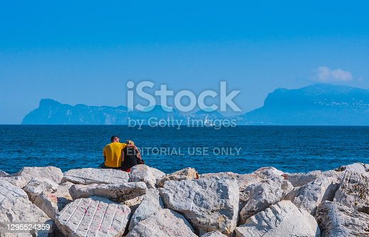 Naples, Italy - may 27: Summer day on the Mediterranean coast. Couple in love on the waterfront looking at the silhouette of the island of Capri in the distance. May 27, 2012. Naples, Campania, Italy.