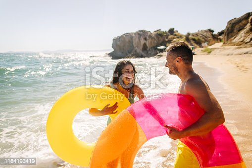 Photo of smiling couple having fun at the beach