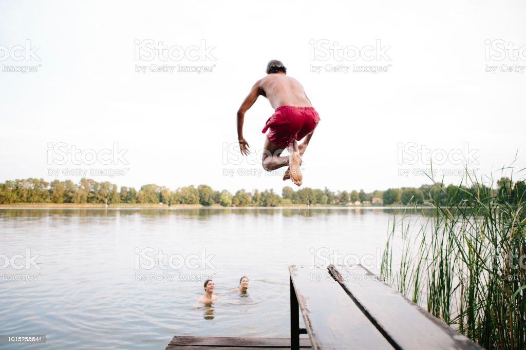 Sommertag: drei junge Erwachsene springen von der Anlegestelle in See – Foto