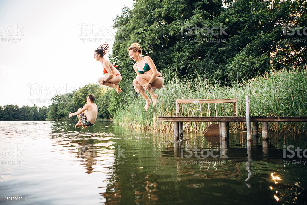 summer day: three young adults jump from jetty into lake stock photo