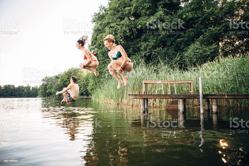 Sommer Tag: Drei junge Menschen springen in See von jetty – Foto