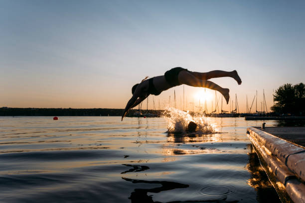 Summer day: young woman jump from jetty into lake while sunset stock photo