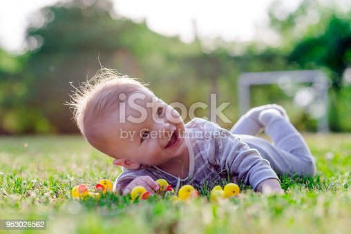 Cute funny laughing Caucasian baby boy learning to crawl, having fun playing on the lawn watching summer flowers in the garden during bright sunny day. Photo of smiling small 6 months old boy in green grass - he smiles and has fun while looking up. Happy young baby lying on tummy in nature with Beautiful little yellow duckling toys around.