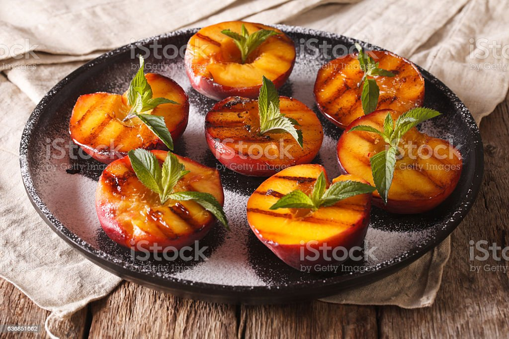 Summer dessert: grilled Peaches with powdered sugar and fresh mint stock photo