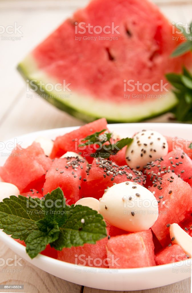 Summer dessert with slices of ripe watermelon, mozzarella, chia seeds and mint on blue wooden background. Healthy vegetarian food concept. royalty-free stock photo