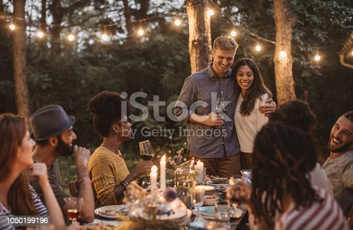 Multi ethnic group of friends have dinner party on porch, everyone enjoy in food, drinking and smiling