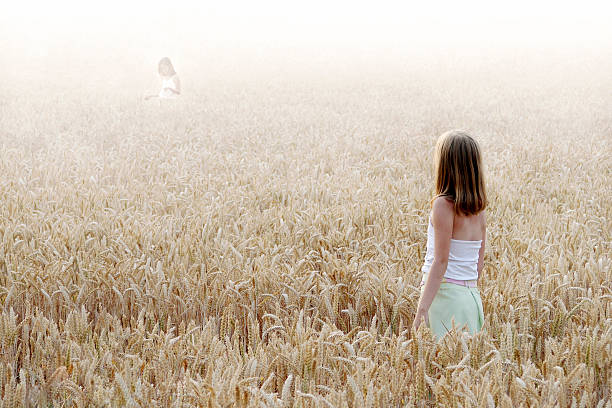 Summer dream Two little mysterious girls standing among wheatears. arcane stock pictures, royalty-free photos & images