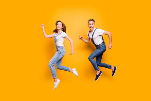 Summer dreamy student freedom fly teen age youth person concept. Side view full size length photo portrait of two cheerful rejoicing attractive handsome guy lady making movement isolated background Summer dreamy student freedom fly teen age youth person concept. Side view full size length photo portrait of two cheerful rejoicing attractive handsome guy lady making movement isolated background bib overalls stock pictures, royalty-free photos & images