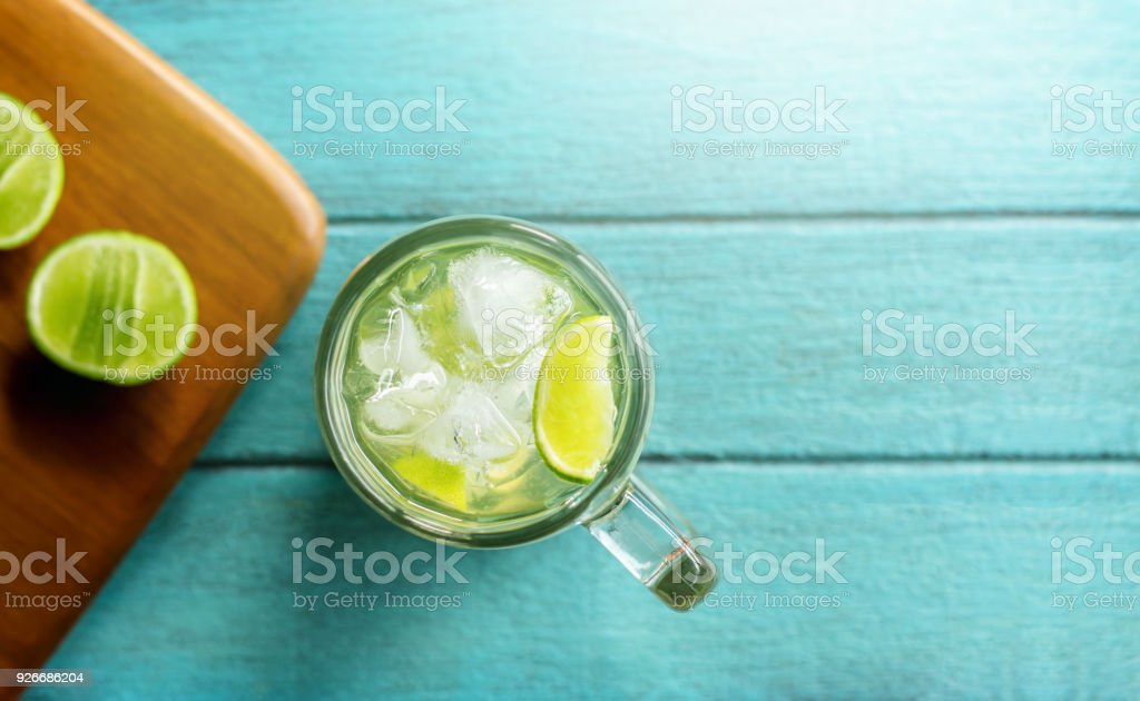 Summer Drink Concept, Glass of Caipirinha or Tropical Lemon Juice with Ice. Lay on Bright Blue Wooden Table. Top View stock photo