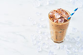 istock Summer drink ice coffee with cream in a tall glass with straw 1089810492