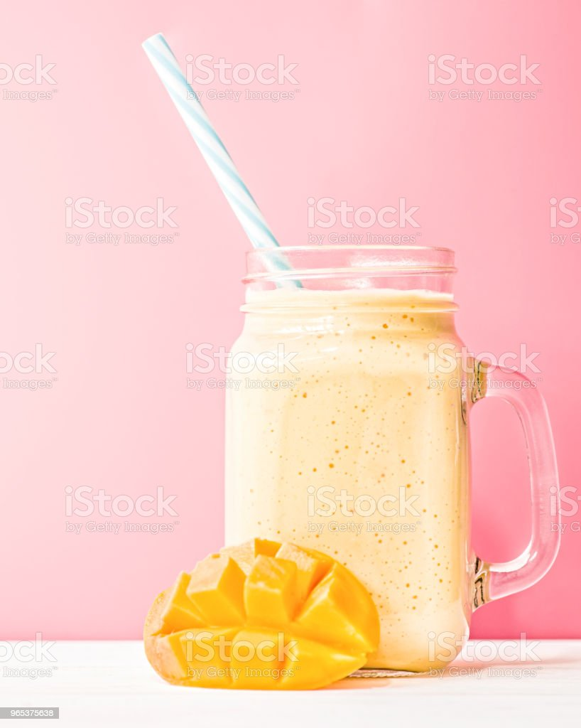 summer drink mango milkshake in mason jar with drinking straw decorated with a half of mango on blue background royalty-free stock photo