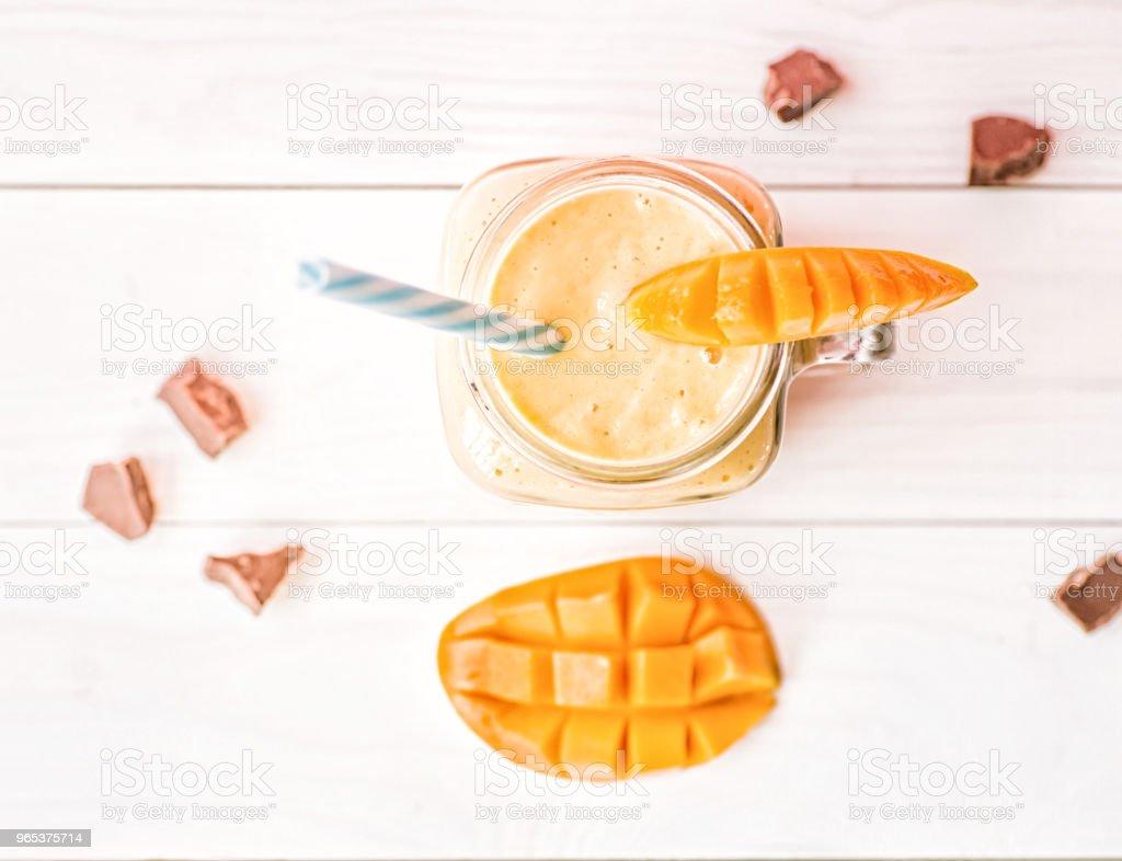 망고의 절반으로 장식 하는 빨 대를 마시는 메이슨 항아리에 여름 음료 망고 밀크, 초콜릿 조각 플랫 하다 소박한 흰색 배경에 평면도 - 로열티 프리 과일 스톡 사진