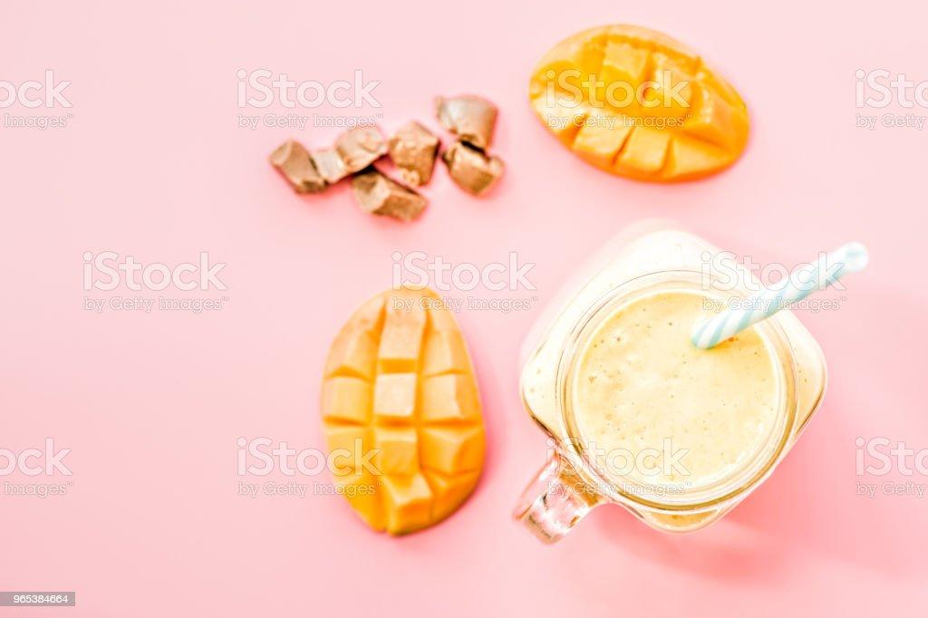 夏天喝芒果奶昔在梅森罐子與喝的稻草裝飾一半芒果, 巧克力片平躺在粉紅色背景上的頂部視圖 - 免版稅一片圖庫照片