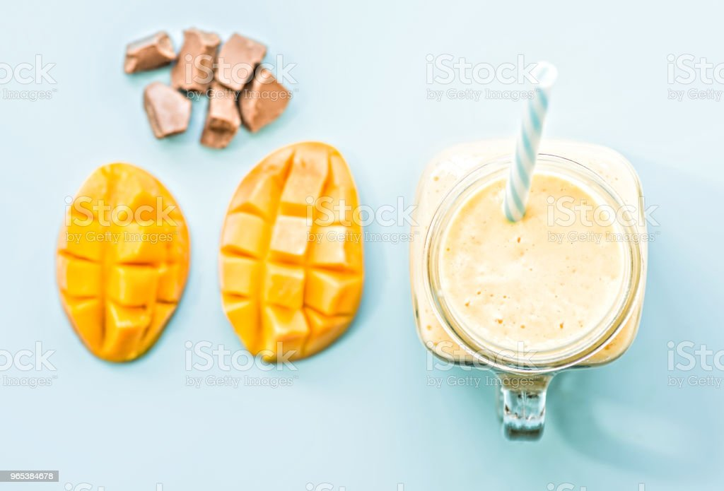 summer drink mango milkshake in mason jar with drinking straw decorated with a half of mango, chocolate pieces flat lay top view on blue background royalty-free stock photo