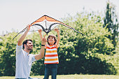 Father and son with a kite outdoors on a sunny day