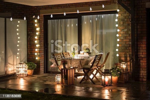 Summer evenig terrace with candles, wine and lights, wet pavements