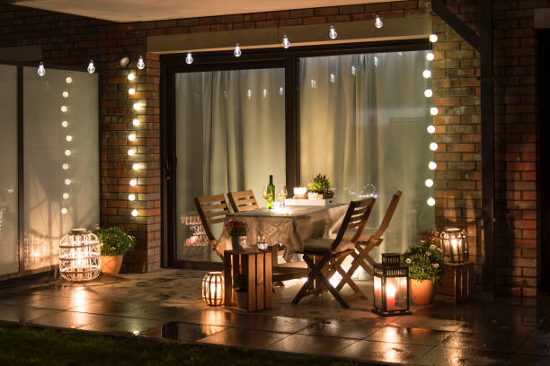Summer evenig terrace with candles, wine and lights Summer evenig terrace with candles, wine and lights, wet pavements lawn stock pictures, royalty-free photos & images