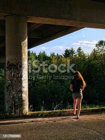 Behind view of teenage girl with beautiful long hair, walking under a concrete road bridge on a beautiful summer evening near her home. Wildflowers and green forests can be seen in the background. Taken in northern Wisconsin.