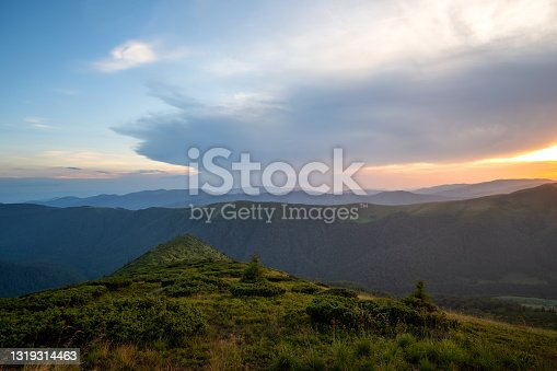 Summer evening mountain landscape with grassy hills and distant peaks at colorful sunset.