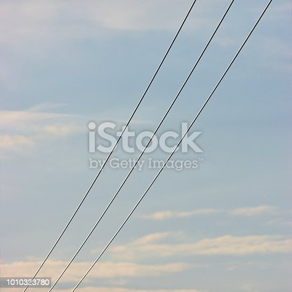 Summer evening sky background, vertical bright blue skyscape copy space, three power line cable wires, pink pastel clouds cloudiness cloudscape, 3 diagonal cables cloudy perspective, scenic golden hour twilight clouding pattern, gentle bokeh