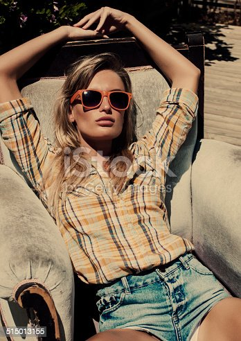 Summer fashion blond women sitting on a street. Summer day. Grain added
