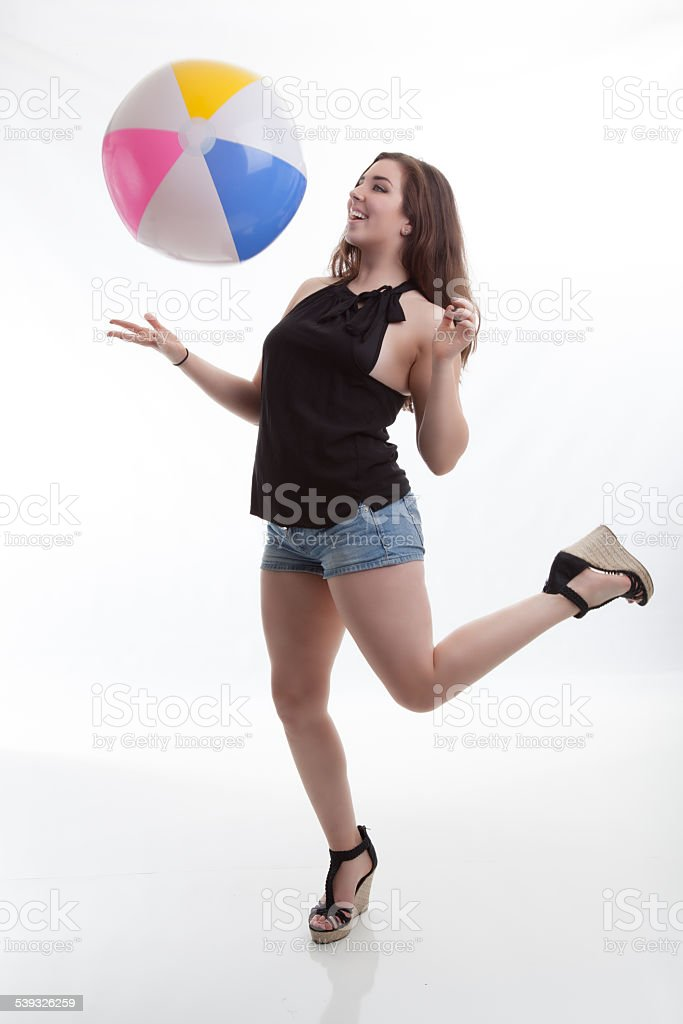 Summer Fashion Model Catches Beach Ball in Cute Outfit stock photo