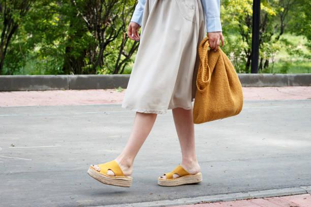 roupa da forma do verão. menina no vestido, sapatas amarelas e saco feito malha na moda, vista lateral - sandália - fotografias e filmes do acervo